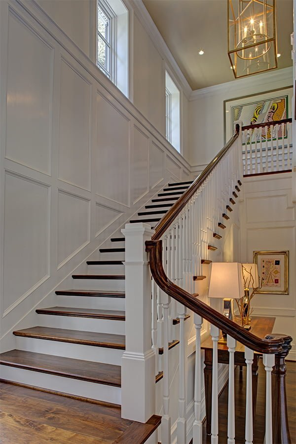 Transitional staircase with medium hardwood flooring and treads, white balusters, and white wall paneling and color