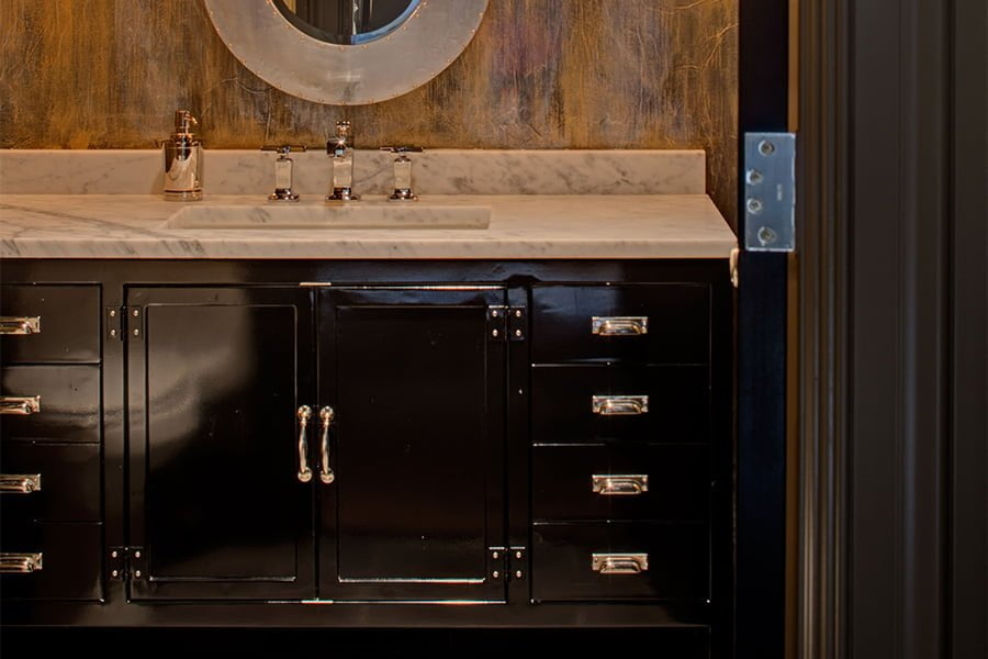High end bathroom sink with dark cabinetry, marble countertops, and textured brown backsplash
