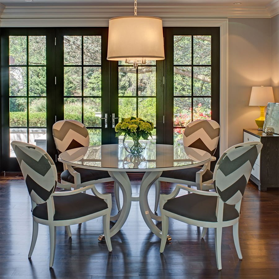 Modern dining set with glass table and matching white wood chairs on dark hardwood flooring