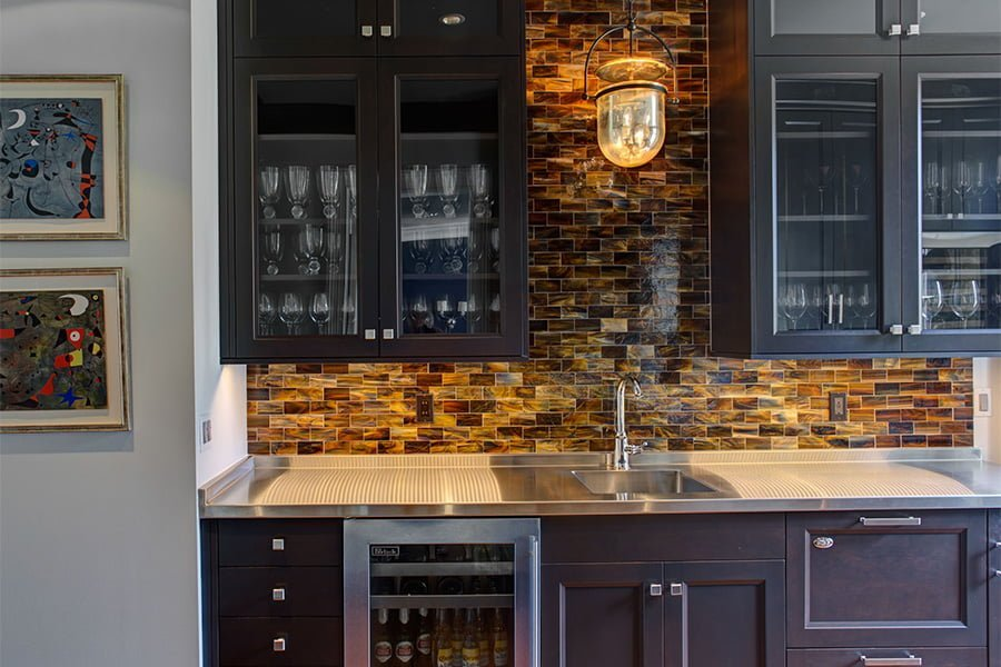Transitional kitchenette with dark cabinetry, stainless steel countertop and appliances, and orange mosaic tile backsplash (2)