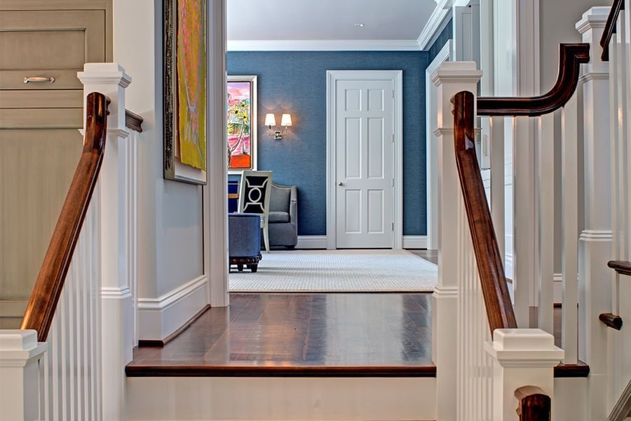 Transitional staircase view with medium hardwood flooring and railings, white balusters and and blue wall color
