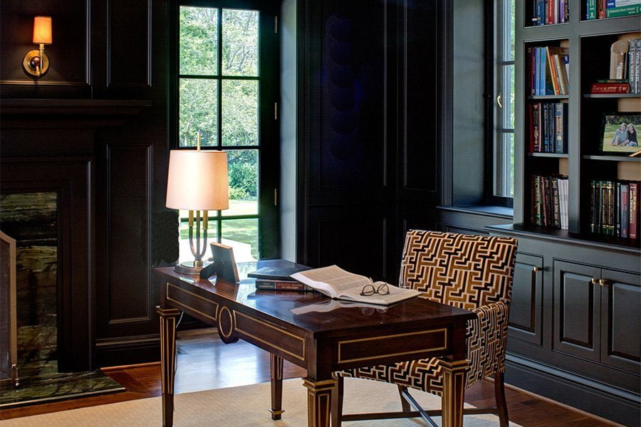 Transitional office space with ornate wood desk table with gold trim, black cabinetry, black and gold cushioned chair, and medium hardwood flooring