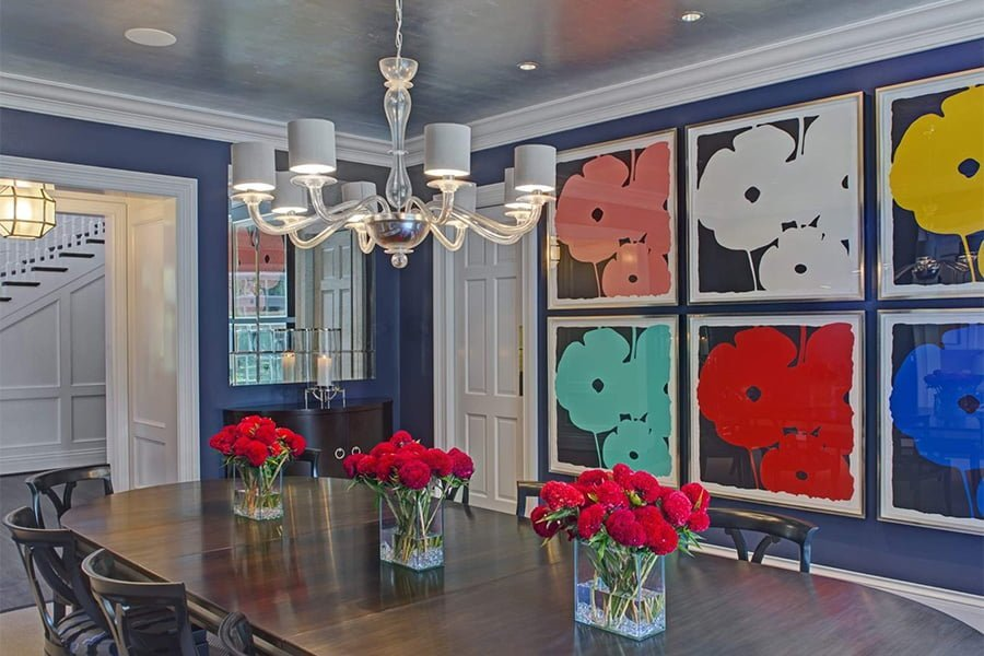 Transitional dining room with dark wood table, blue wall color, and decorative floral paintings on the wall