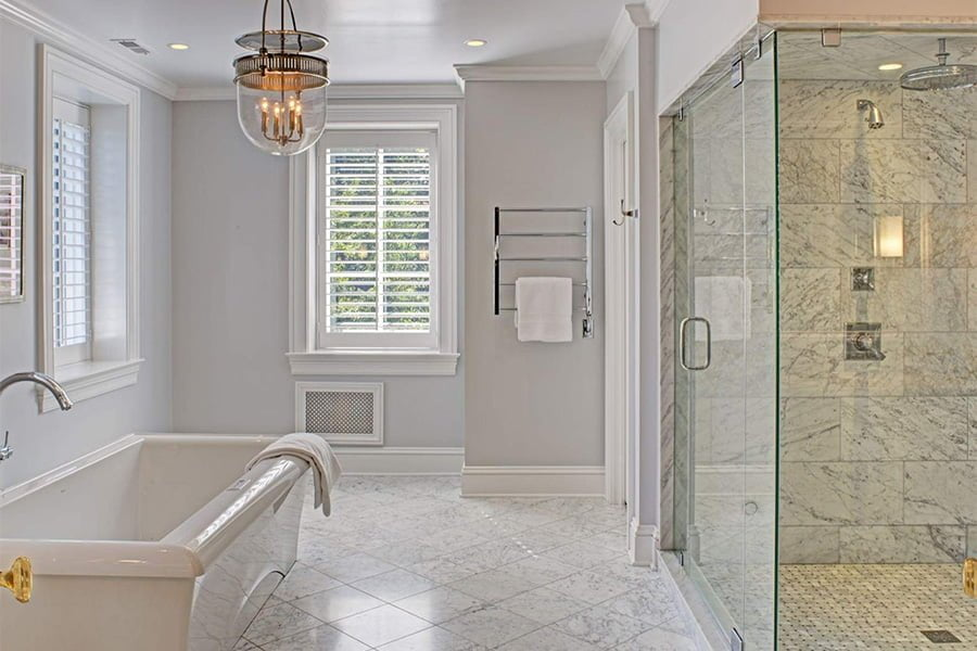 Transitional bathroom with all glass shower, marble tile flooring and backsplash, and minimal color scheme