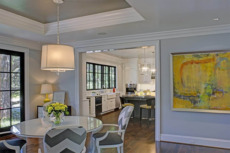 Transitional/modern space with custom white cabinetry, granite countertops, stainless steel appliances, dark hardwood flooring and grey island cabinetry; View into kitchen from dining room