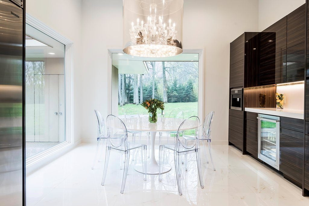 Modern kitchen with custom brown cabinetry and white marble dinner, plastic table and plastic chairs