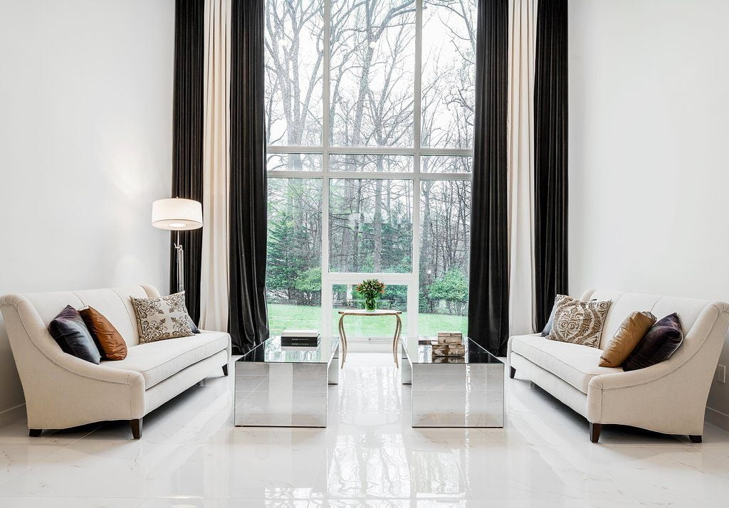Modern living room area with minimal furniture, reflective coffee tables, all white marble flooring (different angle)