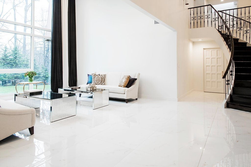 Modern living room area with minimal furniture, reflective coffee tables, all white marble flooring