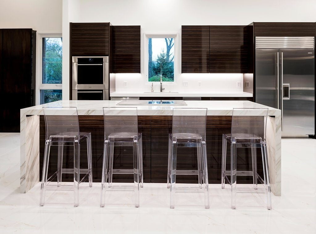 Modern kitchen and island with dark hardwood cabinetry, white marble countertops and flooring, clear plastic hi-top chairs