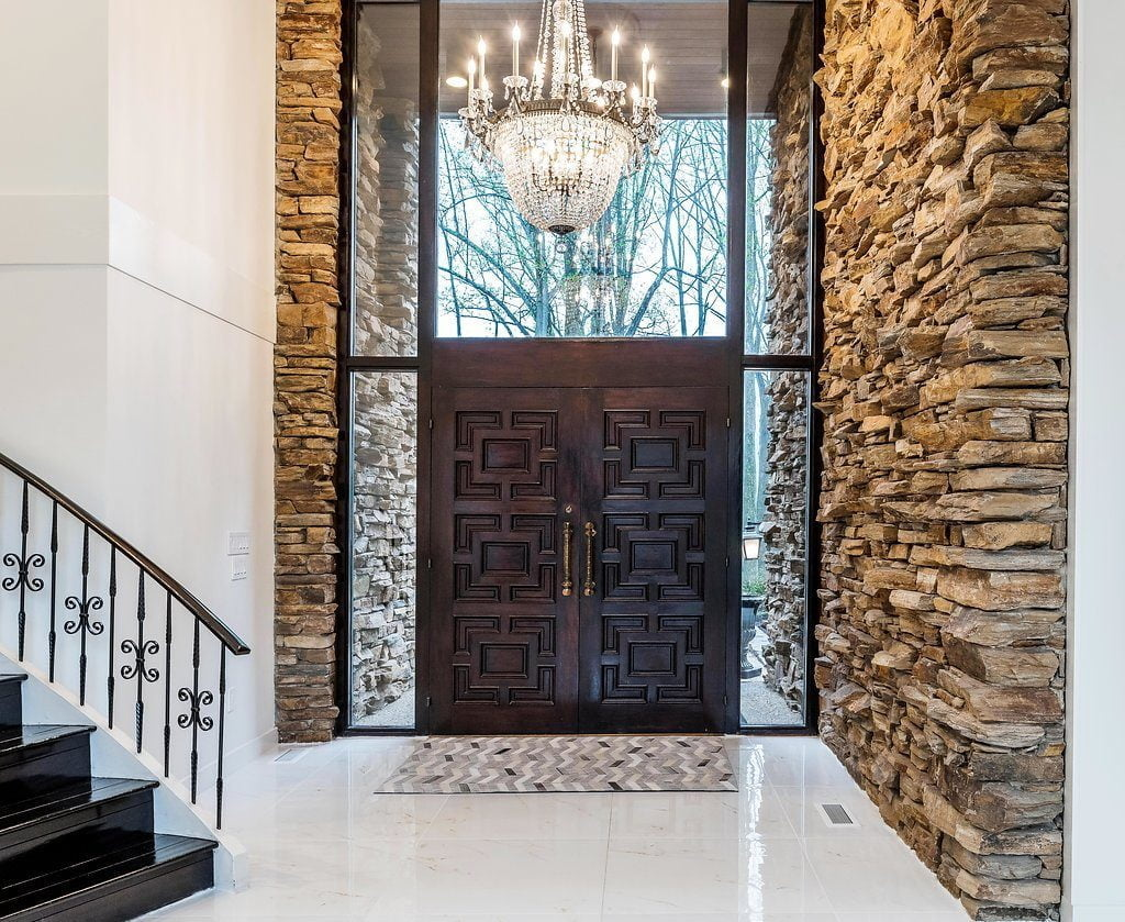 Modern entrance with 2 big dark wood doors surrounded by glass and cobblestone that comes in from outside