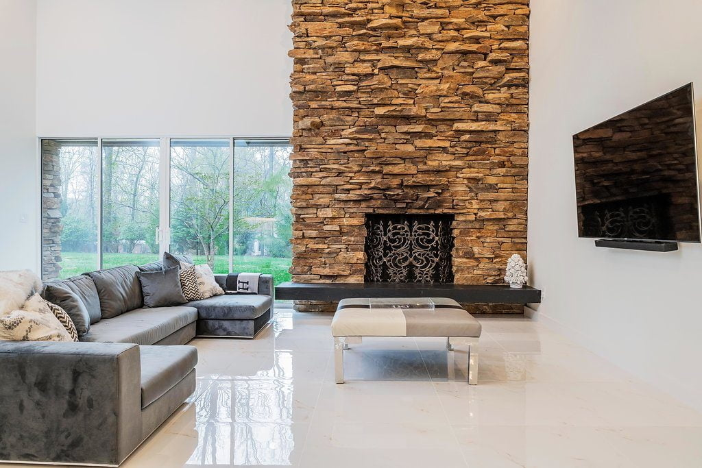 Open/modern family room with cobblestone fireplace, minimal furniture, white tile flooring, and black fireplace slab