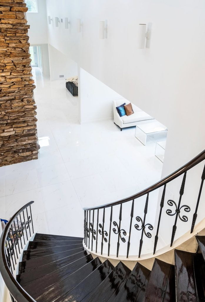 Elegant staircase with metal railings and decorative balusters, and dark hardwood treads, leading to white marble flooring