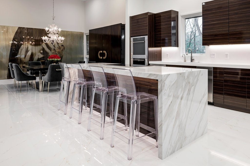 Modern style kitchen with dark hardwood cabinetry, white marble countertops and flooring, stainless steel appliances (back angle)