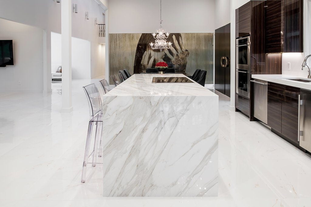 Modern style kitchen with dark hardwood cabinetry, white marble countertops and flooring, stainless steel appliances (side angle)