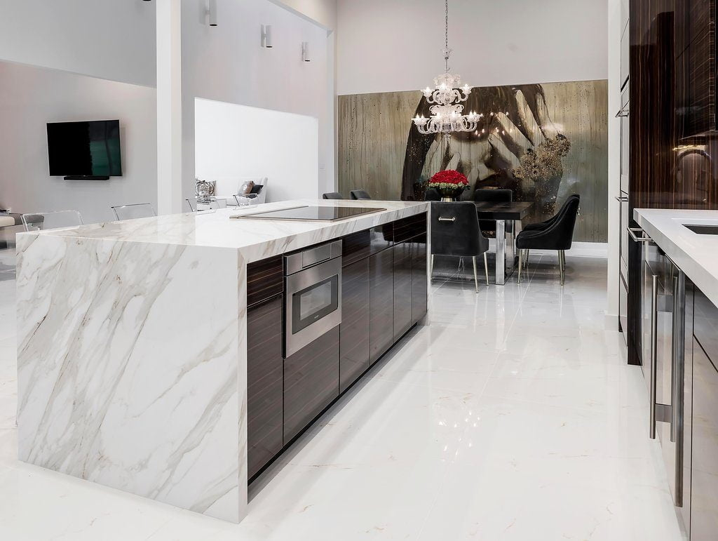 Modern style kitchen with dark hardwood cabinetry, white marble countertops and flooring, stainless steel appliances