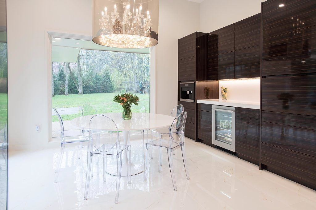 Modern kitchen with custom brown cabinetry and white marble dinner, plastic table and plastic chairs (2)