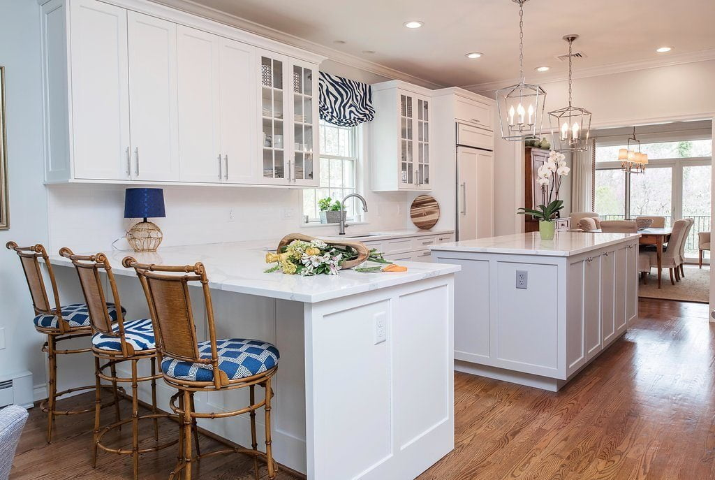 High end kitchen with white cabinetry and marble countertops, stainless steel sink, and medium hardwood flooring (zoomed out)