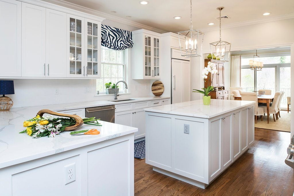High end kitchen with white cabinetry and marble countertops, stainless steel sink, and medium hardwood flooring