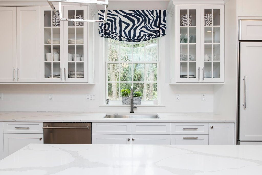 High end kitchen with white cabinetry and marble countertops, stainless steel sink, and glass-incorporated cabinets