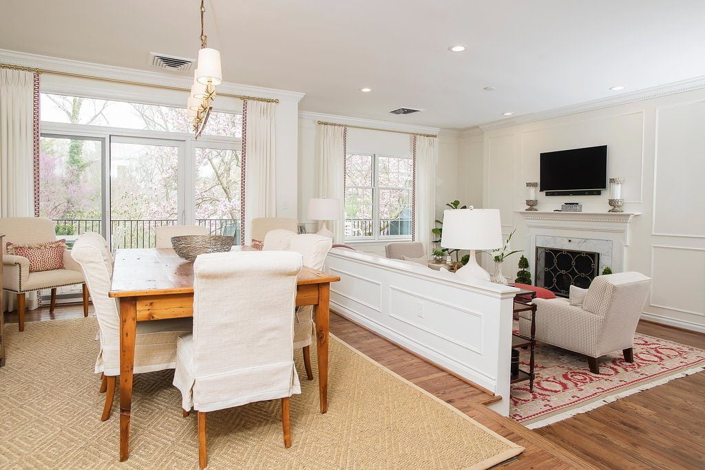 Traditional family room set down from the dining room, with off-white furniture color and vibrantly patterned red carpet (zoomed out)