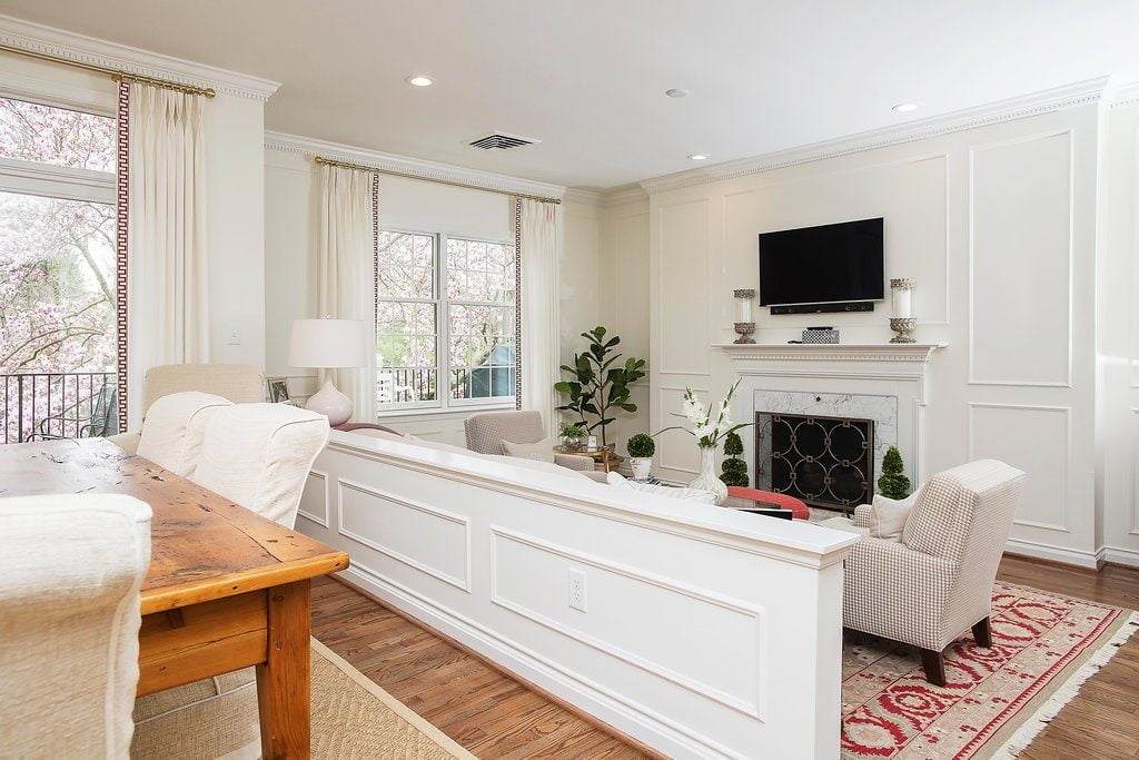 Traditional family room set down from the dining room, with off-white furniture color and vibrantly patterned red carpet (different angle)