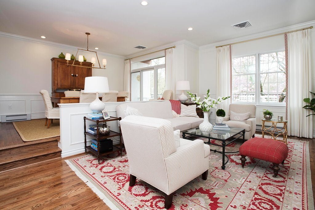 Traditional family room set down from the dining room, with off-white furniture color and vibrantly patterned red carpet (2)
