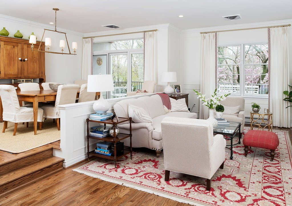 Traditional family room set down from the dining room, with off-white furniture color and vibrantly patterned red carpet