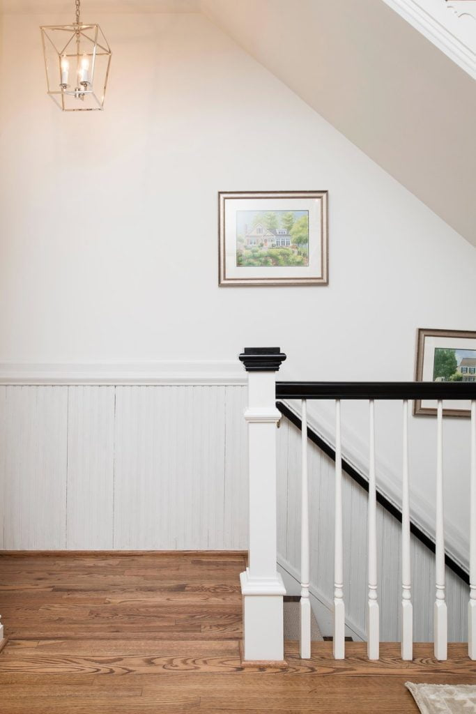 Transitional staircase (from upstairs) with white balusters and black railings and post cap