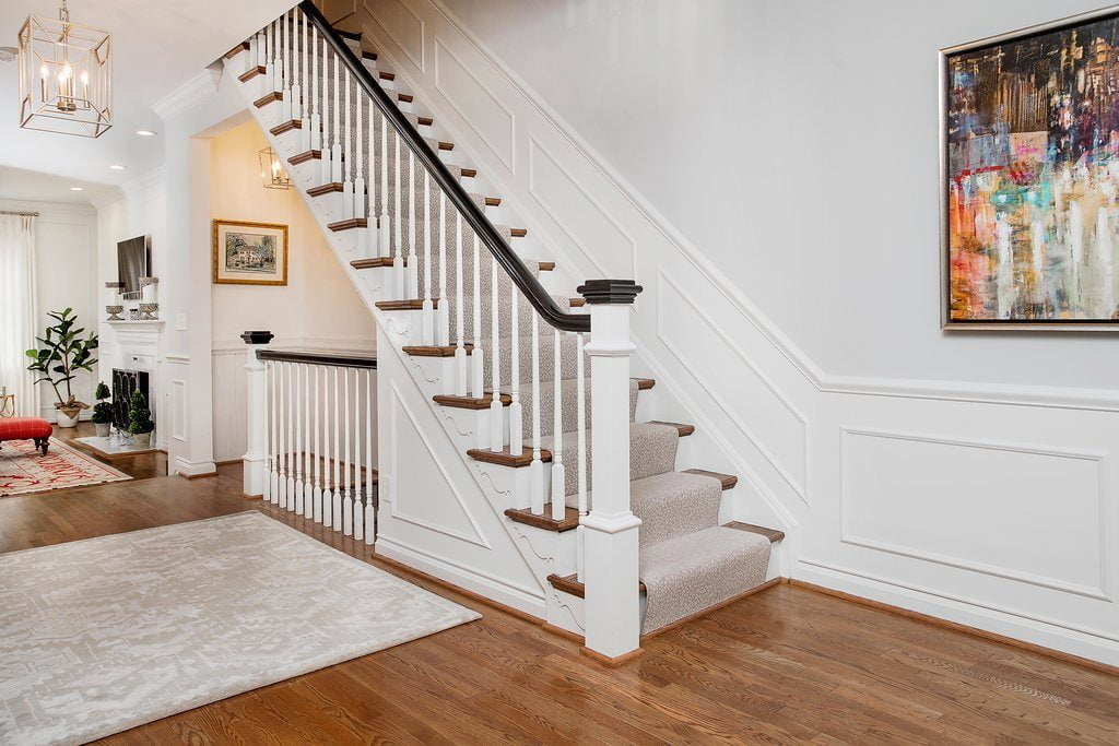 Transitional staircase with dark wood post cap and railings, medium hardwood treads, and white balusters