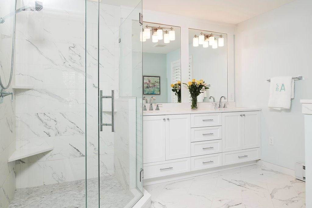 High end bathroom sinks with white cabinetry and marble countertops (zoomed out) with glass shower