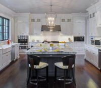 Open concept kitchen with white cabinetry, a gray center island and gray and white marble countertops.