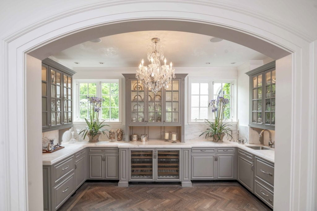 Traditional kitchen area with custom light grey cabinetry, marble countertops, ornate crystal chandelier, and dark chevron hardwood flooring