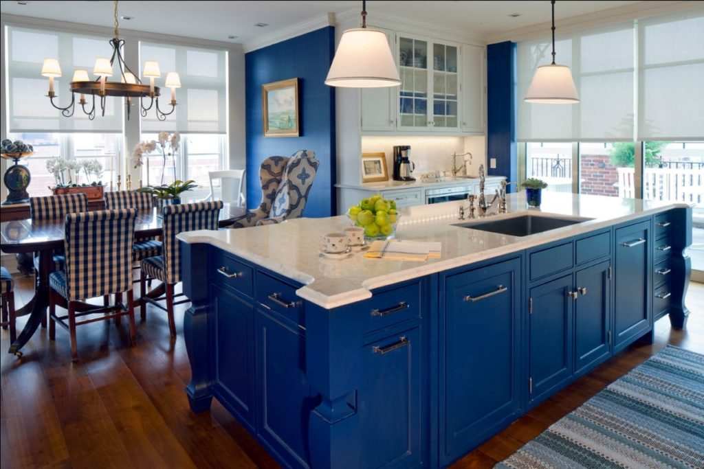 Transitional kitchen/dining room with medium hardwood flooring and custom navy island drawers and navy accent wall