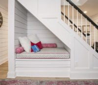 Triangular sitting nook with white paneling and cushions underneath staircase