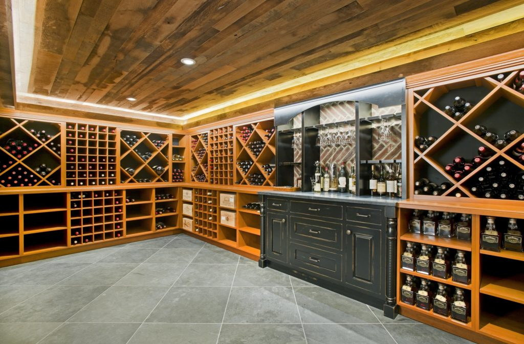 Custom built in-home wine cellar with floor-to-ceiling cabinetry and a wood paneled ceiling.