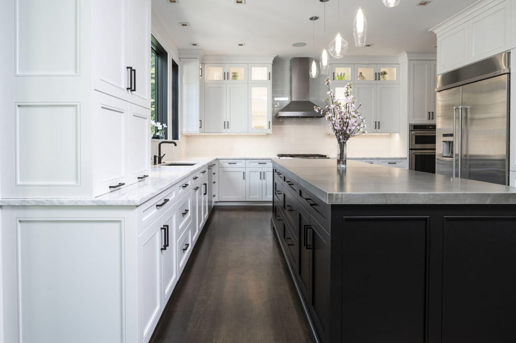 Modern kitchen remodel with an open concept layout including white cabinetry, marble countertop and a dark wood center island.
