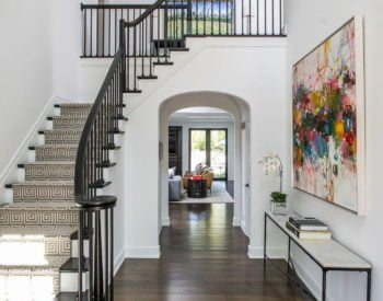 Open-concept entryway with stairs, dark wood floors and arched doorways in a modern home.