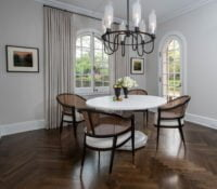 Remodeled dining area with a modern chandelier, dining table and chairs with dark wood chevron flooring and arched windows.