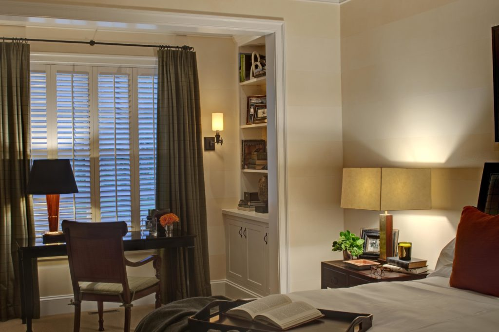 Bedroom with a corner office nook including built-in shelving and cabinetry next to a window.