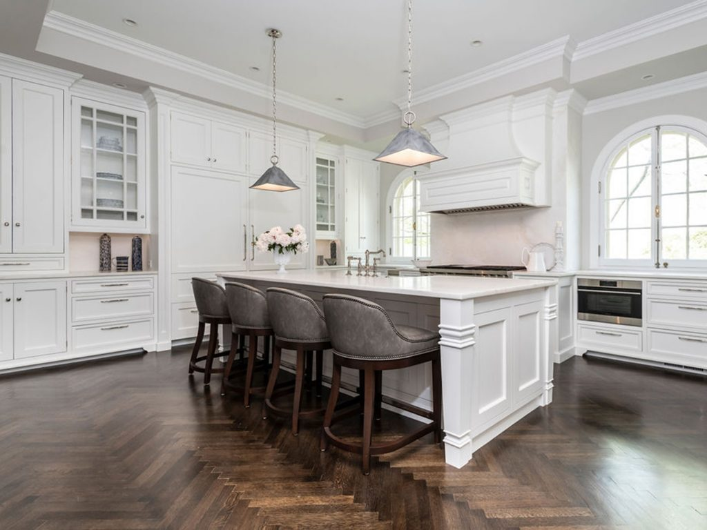 Transitional kitchen with white cabinetry, patterned dark hardwood flooring, marble countertops, and custom pyramidal hanging floodlights