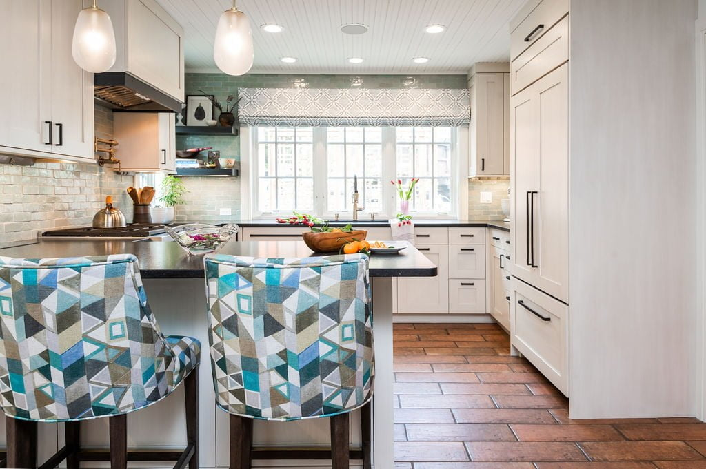 Transitional kitchen with custom white cabinetry, brown terra-cotta tile flooring, dark marble countertops, and blue-green accents on walls and hi-top chairs