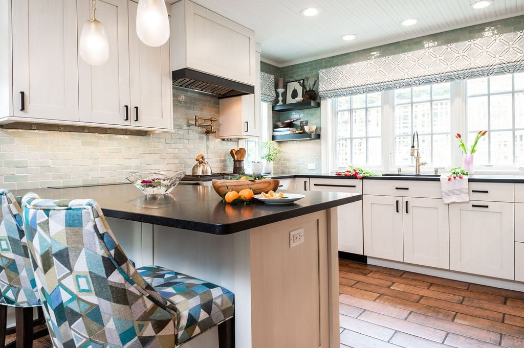 Transitional kitchen with custom white cabinetry and dark marble countertops, brown terra-cotta tile flooring, and a green-hue tile backsplash (Zoomed all the way out)