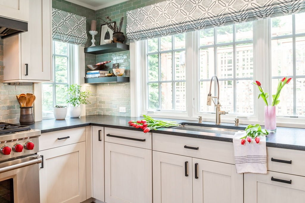 Transitional kitchen sink with custom white cabinetry and dark marble countertops, and a green-hue tile backsplash (Zoomed out)