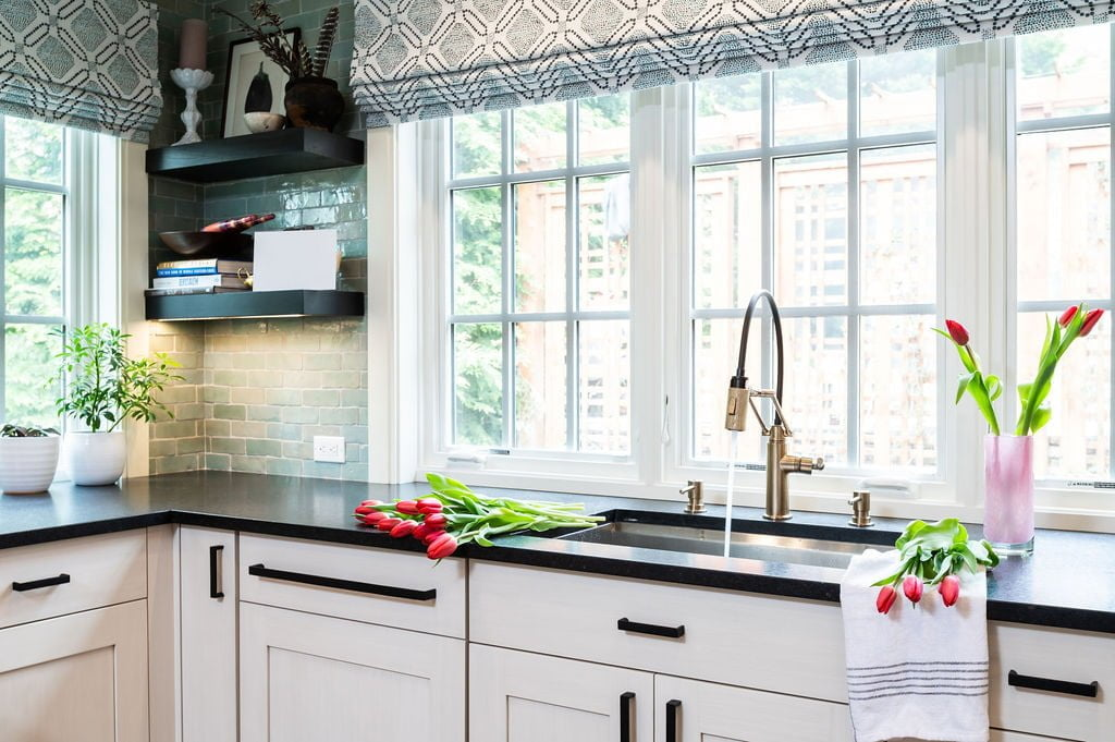 Transitional kitchen counter with white cabinetry and dark marble countertops, with light green tile backsplash, black wooden floating shelves, and stainless steel sink
