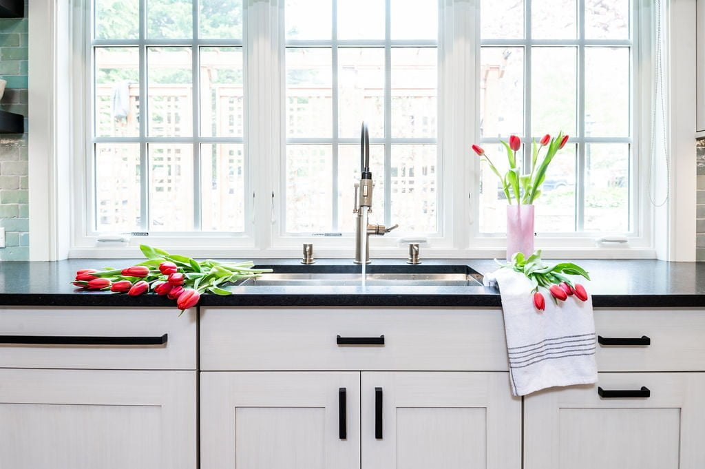 Transitional stainless steel kitchen sink with custom white cabinetry and dark marble countertops