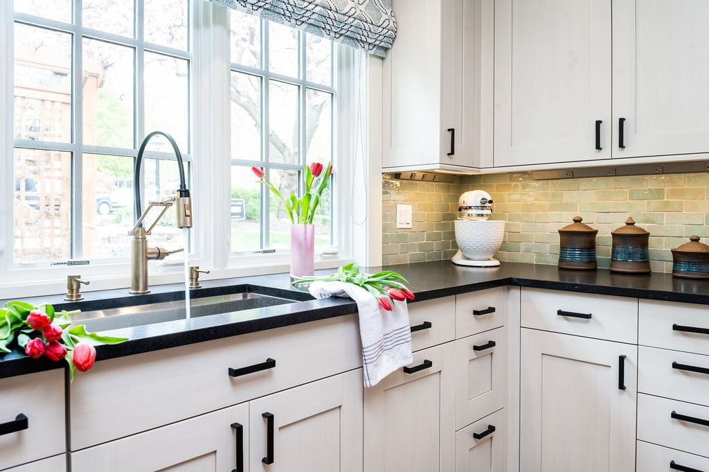 Transitional custom white cabinetry with dark marble countertops, and light green tile backsplash (Other view)