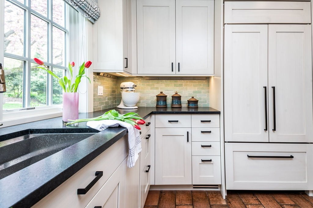 Transitional custom white cabinetry and decor for refrigerator, with brown terra-cotta tile flooring and light green tile backsplash (Other view)