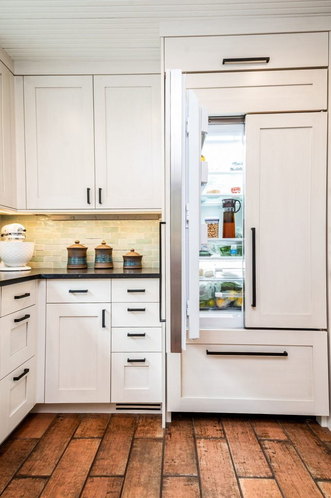 Transitional custom white cabinetry and decor for refrigerator, with brown terra-cotta tile flooring and light green tile backsplash
