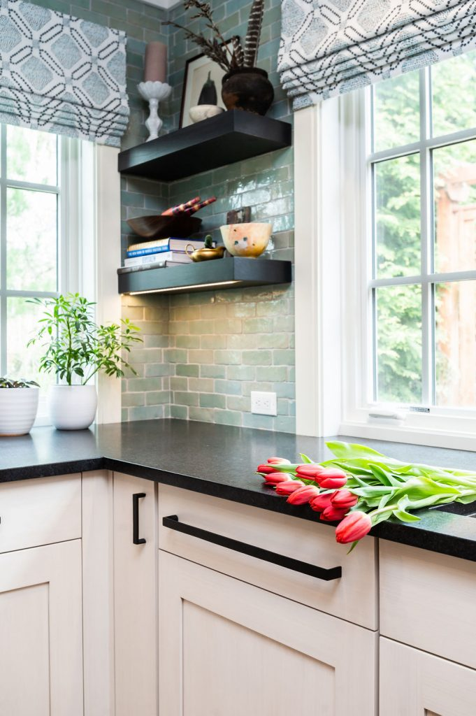 Transitional kitchen counter with white cabinetry and dark marble countertops, with light green tile backsplash and black wooden floating shelves