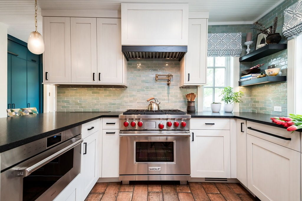 Kitchen with white custom cabinetry, dark marble countertops, white paneling on ceiling, stainless steel appliances, light green tile backsplash, and hanging lights (Different view)